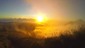Salida del sol de oro a través de las nubes sobre el lago Batur con la visión desde el pico del volcán de Batur GoPro HD Bali, In metrajes