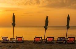 Salida del sol debajo del parasol en la playa Imagen de archivo