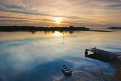 Salida del sol del invierno sobre un río vidrioso con el barco y J Fotografía de archivo
