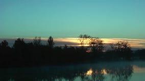 Salida del sol detrás de la reflexión del bosque en el lago almacen de metraje de vídeo