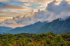 Salida del sol detrás de las nubes grandes sobre la montaña Imagenes de archivo