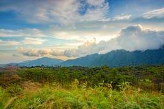 Salida del sol detrás de las nubes grandes sobre la montaña Foto de archivo libre de regalías