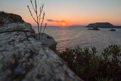 Salida del sol detrás del acantilado en el mar Fotografía de archivo