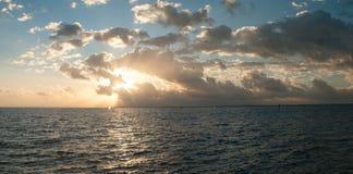 Salida del sol dramática sobre el agua; panorama Imagenes de archivo
