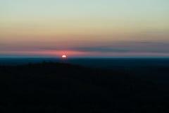 Salida del sol dramática sobre bosque oscuro Foto de archivo