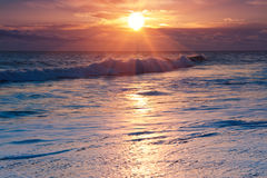 Salida del sol dramática sobre la resaca del océano Fotos de archivo