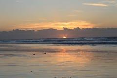Salida del sol durante la bajamar en la bahía Londres del este de Morgan en la costa salvaje de Suráfrica imagenes de archivo