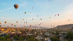 Salida del sol en Cappadocia con el globo del vuelo en el horizonte en Goreme, lapso de la ciudad de Cappadocia de tiempo de Turq metrajes