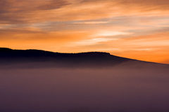 Salida del sol en colores anaranjados cerca de Underberg en la cordillera de Drakensberg en Suráfrica Imagenes de archivo