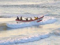 Salida del sol en Durban, Suráfrica; captura de un bote de remos de la jábega-red en la acción Fotografía de archivo