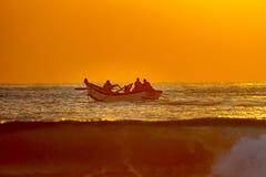 Salida del sol en Durban, Suráfrica; captura de un bote de remos de la jábega-red en la acción Fotos de archivo
