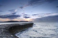 Salida del sol en el Cobb en Lyme Regis imagen de archivo libre de regalías