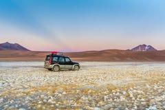 Salida del sol en el desierto de Atacama y sus volcanes con un coche foto de archivo