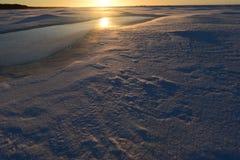 Salida del sol en el desierto nevoso en el golfo de Finlandia Foto de archivo