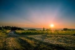Salida del sol en el extremo del camino imagenes de archivo