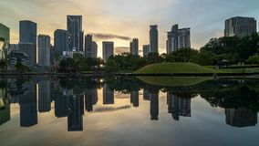 Salida del sol en el horizonte de la ciudad de Kuala Lumpur con la reflexión en el agua almacen de metraje de vídeo