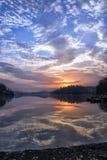 Salida del sol en el lago con las nubes Foto de archivo