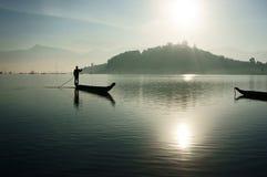Salida del sol en el lago, pescador que rema el barco Imagenes de archivo
