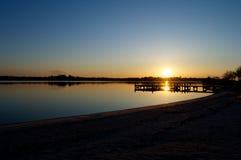 Salida del sol en el muelle en el río Fotografía de archivo libre de regalías