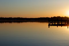 Salida del sol en el muelle en el río Foto de archivo