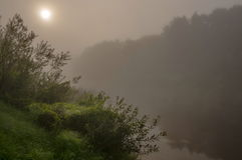 Salida del sol en el río en una niebla foto de archivo