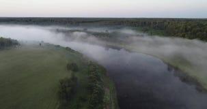 Salida del sol en el río, visión aérea 4K de la niebla de la mañana en la salida del sol, rayos anaranjados del sol a través de l metrajes