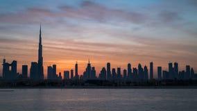 Salida del sol en el timelapse de Dubai, amanecer sobre Burj Khalifa Nuevo día en Dubai debajo del sol, cielo nublado coloreado h metrajes
