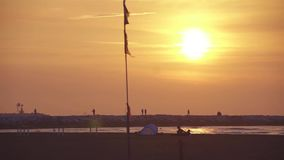 Salida del sol en la orilla del mar, delante de un guijarro adonde la gente pasa cerca almacen de video