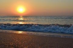Salida del sol en la playa con las ondas y reflexiones grandes de un sol en la arena Foto de archivo