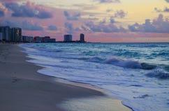 Salida del sol en la playa contra rascacielos Fotografía de archivo