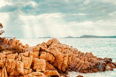 Salida del sol en la playa de Capriccioli y las aguas azules foto de archivo