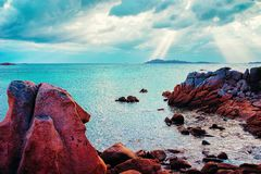Salida del sol en la playa de Capriccioli y las aguas azules fotografía de archivo