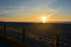 Salida del sol en la playa de detrás las dunas Fotos de archivo