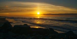 Salida del sol en la playa de la locura Fotos de archivo