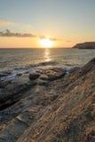 Salida del sol en la playa rocosa Imagenes de archivo