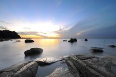 Salida del sol en la playa tropical rocosa Imágenes de archivo libres de regalías