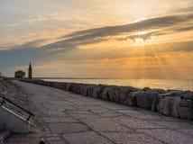 Salida del sol en la 'promenade' de Caorle Italia Caorle, faro Imagen de archivo