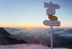 Salida del sol en montañas nevosas con las nubes onduladas Foto de archivo libre de regalías