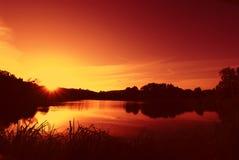 Salida del sol en un lago Imagenes de archivo