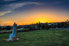 Salida del sol en un parque de la ciudad con la estatua de piedra Foto de archivo