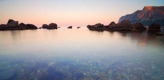 Salida del sol en una bahía del mar tranquilo con las rocas y las montañas Fotos de archivo