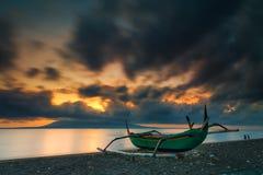 Salida del sol en una playa con el barco de pesca en el primero plano Imagen de archivo libre de regalías