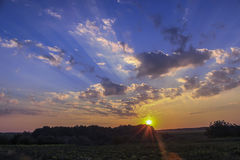 Salida del sol entre campos verdes Fotos de archivo libres de regalías