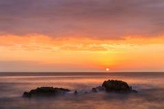 Salida del sol entre dos rocas en la costa del pueblo de Tossa de Mar Imágenes de archivo libres de regalías