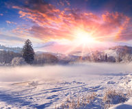 Salida del sol hermosa del invierno en pueblo de montaña.