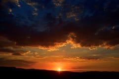 Salida del sol hermosa detrás de las nubes y de las montañas Imagen de archivo libre de regalías