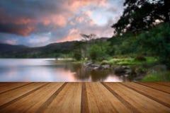 Salida del sol hermosa sobre el lago y las montañas con flo de madera de los tablones Fotos de archivo libres de regalías