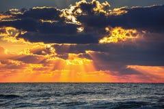 Salida del sol hermosa sobre el mar La salida del sol colorida de la playa del océano con el cielo azul y el sol profundos irradi Fotografía de archivo libre de regalías