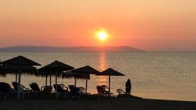Salida del sol hermosa sobre el mar y una mujer en la playa Nea Vra Imagen de archivo libre de regalías