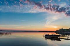 Salida del sol del lago cottage con el barco en el muelle foto de archivo libre de regalías